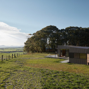 Design ideas for a contemporary one-storey black house exterior in Melbourne with metal siding and a shed roof.