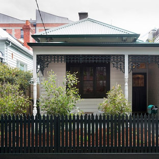 Example of a small eclectic white exterior home design in Melbourne with a hip roof