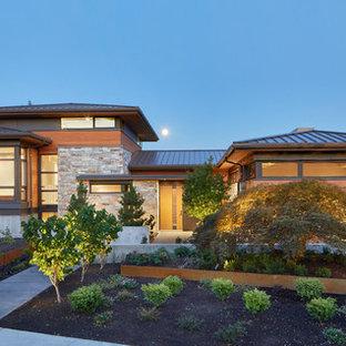 Exempel på ett modernt brunt hus i flera nivåer, med blandad fasad, valmat tak och tak i metall