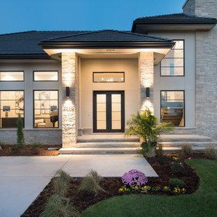 На фото: большой, двухэтажный, бежевый дом в современном стиле с облицовкой из цементной штукатурки и вальмовой крышей с