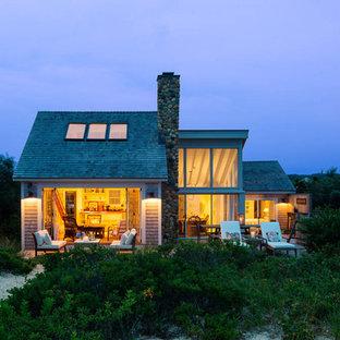 Aménagement d'une façade de maison beige bord de mer de taille moyenne et à un étage avec un revêtement en vinyle et un toit à deux pans.