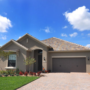Inspiration for a mid-sized tropical gray one-story stucco gable roof remodel in Tampa