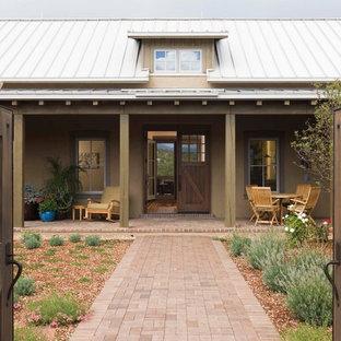 Lantlig inredning av ett mellanstort beige hus, med allt i ett plan, stuckatur, sadeltak och tak i metall