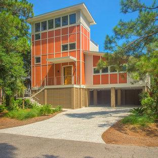 Foto de fachada de casa naranja, costera, de tres plantas, con revestimientos combinados