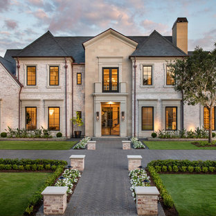 Huge transitional two-story brick exterior home idea in Houston with a tile roof