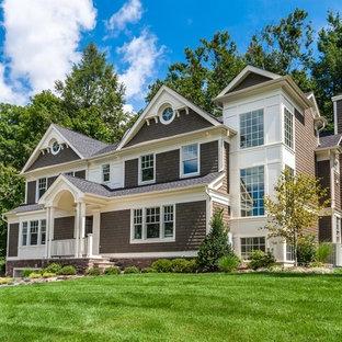 Пример оригинального дизайна: огромный, двухэтажный, деревянный, коричневый дом в стиле фьюжн с двускатной крышей