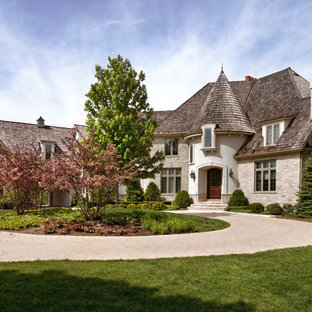 Inspiration for a huge french country beige three-story stone exterior home remodel in Chicago with a hip roof