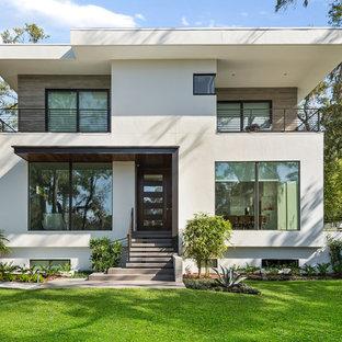 Esempio della facciata di una casa unifamiliare beige contemporanea a due piani con rivestimenti misti e tetto piano