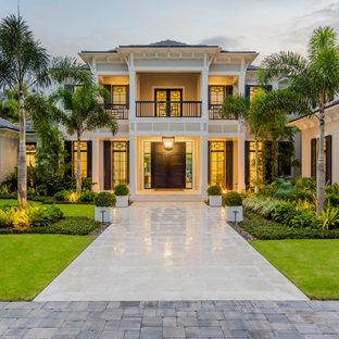 Ejemplo de fachada de casa beige, tropical, de dos plantas, con tejado a cuatro aguas