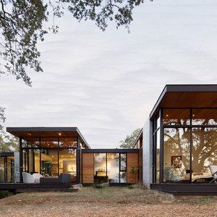 Foto della facciata di una casa contemporanea a un piano con rivestimento in vetro e tetto piano