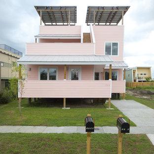 ニューオリンズのコンテンポラリースタイルのおしゃれな二階建ての家 (木材サイディング、ピンクの外壁) の写真