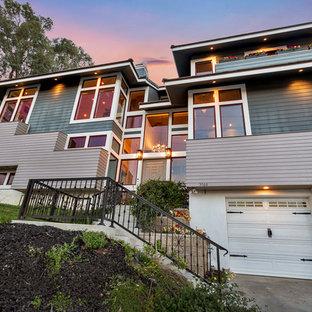 Imagen de fachada de casa gris, vintage, grande, a niveles, con revestimientos combinados, tejado a dos aguas y tejado de teja de barro