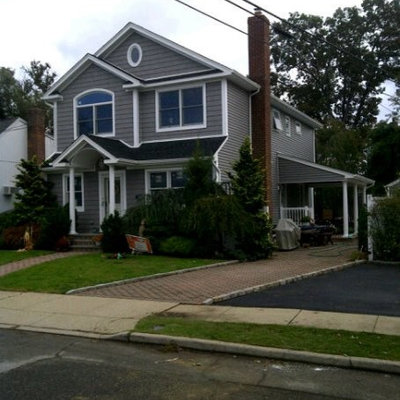 Example of a large classic gray two-story vinyl gable roof design in New York