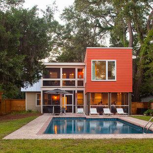 Inspiration pour une façade de maison rouge minimaliste de taille moyenne et à un étage avec un revêtement en panneau de béton fibré et un toit de Gambrel.