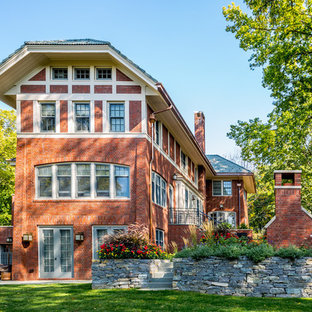 Arts and crafts red three-story brick house exterior photo in Minneapolis with a clipped gable roof and a tile roof