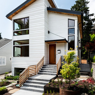 Inspiration for a large contemporary white three-story wood house exterior remodel in Seattle with a shed roof and a metal roof
