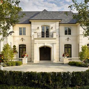 Diseño de fachada beige, tradicional, grande, de dos plantas, con revestimiento de piedra