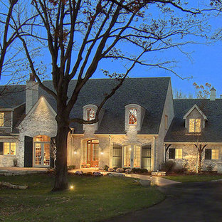 Example of a large classic beige two-story stone exterior home design in Chicago with a shingle roof
