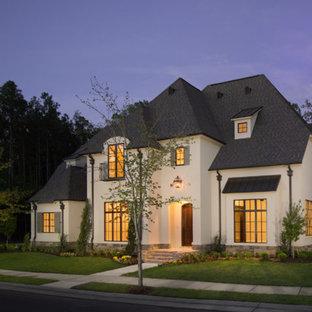 Idee per la facciata di una casa grande bianca a tre piani con rivestimento in stucco e tetto a padiglione
