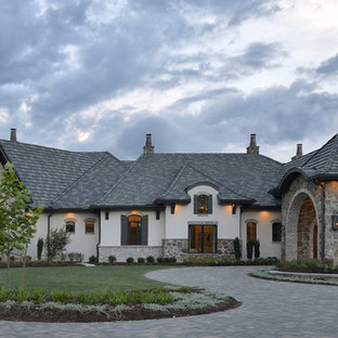 Huge eclectic beige one-story stucco house exterior idea in Houston with a hip roof and a tile roof