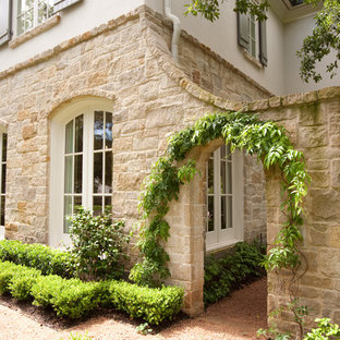 Large traditional beige two-story stone exterior home idea in Houston