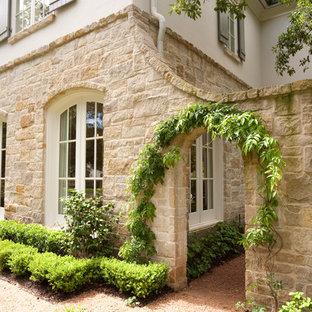 ヒューストンのトラディショナルスタイルのおしゃれな家の外観 (石材サイディング、ベージュの外壁) の写真