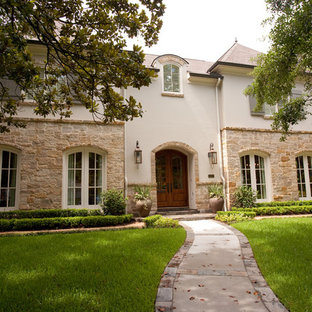 Example of a large french country beige two-story stone exterior home design in Houston