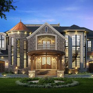 Aménagement d'une très grande façade en pierre beige classique à un étage avec un toit à quatre pans.