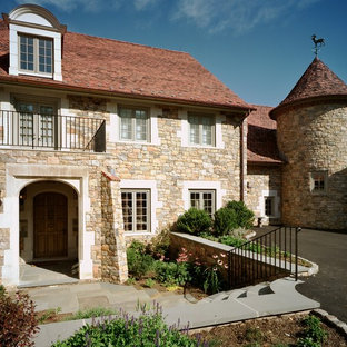 Example of a tuscan stone exterior home design in Philadelphia
