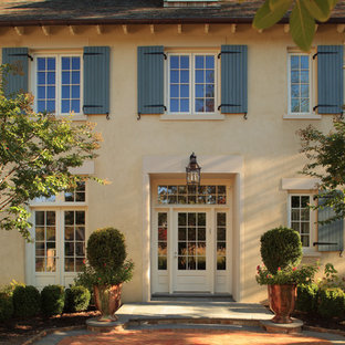 Large french country three-story stucco exterior home idea in DC Metro