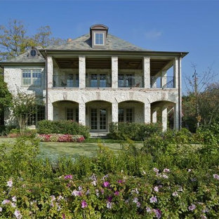 Example of a mid-sized mountain style gray two-story stone gable roof design in Dallas