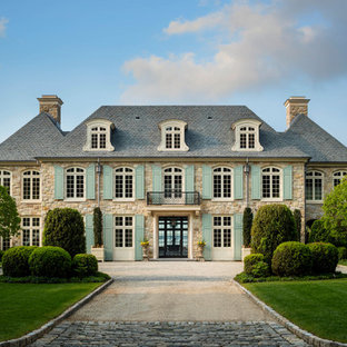 French country beige two-story stone house exterior photo in New York with a hip roof and a tile roof