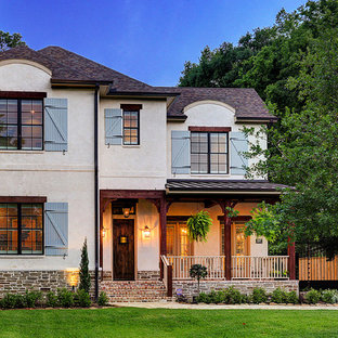 French country beige two-story house exterior photo in Houston with a shingle roof