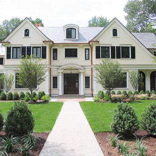 Large french country beige three-story exterior home idea in New York