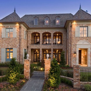 French country three-story brick house exterior photo in Houston with a hip roof