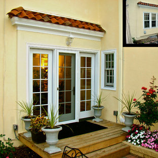 Ejemplo de fachada amarilla, clásica, pequeña, de una planta, con revestimiento de estuco y tejado de un solo tendido