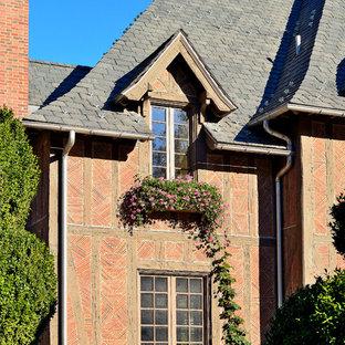 Inspiration pour une façade en brique rouge traditionnelle à deux étages et plus avec un toit à quatre pans.