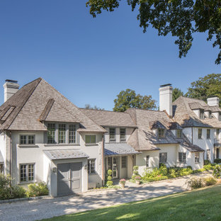 French country white two-story stone house exterior photo in New York with a hip roof