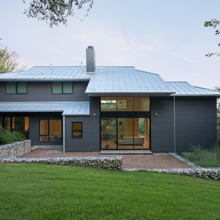 Contemporary gray two-story vinyl house exterior idea in Houston with a hip roof and a metal roof