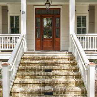 Example of a large beach style beige two-story wood house exterior design in Charleston with a shingle roof