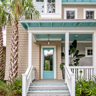 Example of a mid-sized beach style beige two-story wood house exterior design in Jacksonville with a hip roof