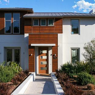 Imagen de fachada blanca, actual, de tamaño medio, de dos plantas, con revestimientos combinados
