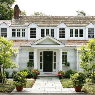 Immagine della facciata di una casa unifamiliare ampia bianca classica a due piani con rivestimento in legno, tetto a capanna e copertura a scandole