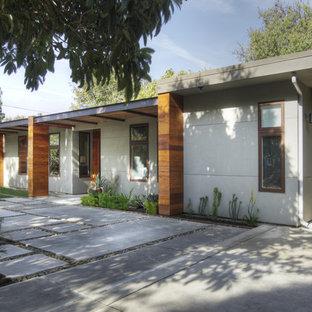 Inspiration för ett mellanstort funkis grått hus, med allt i ett plan och platt tak
