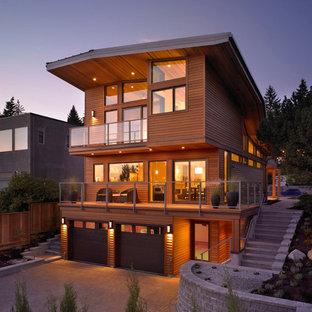 Esempio della facciata di una casa grande moderna a tre piani con rivestimento in legno