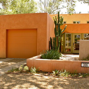 Стильный дизайн: двухэтажный, оранжевый дом с облицовкой из самана и плоской крышей - последний тренд