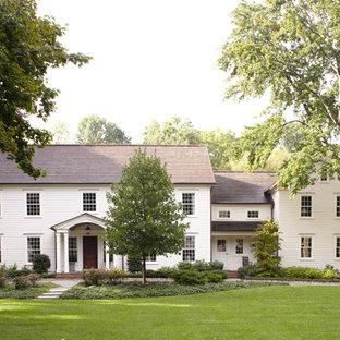 Ejemplo de fachada blanca, clásica, de dos plantas