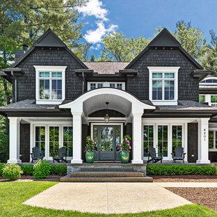Foto della facciata di una casa unifamiliare grande nera stile marinaro a due piani con rivestimento in legno, tetto a capanna e copertura a scandole