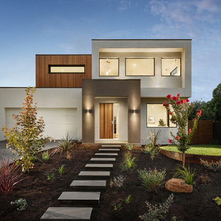 This is an example of a contemporary two-storey white house exterior in Melbourne with a flat roof.