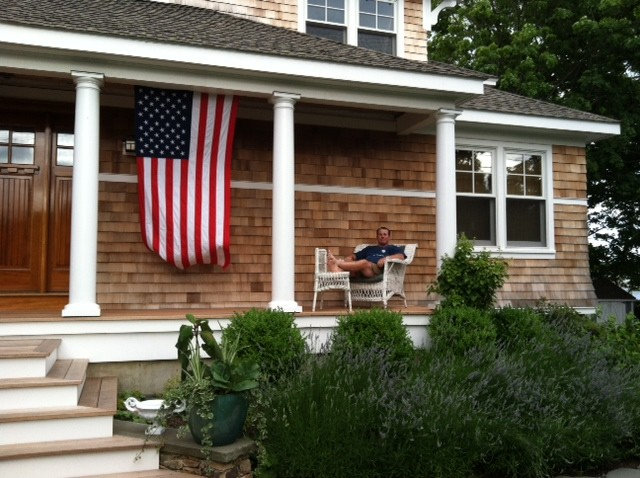Image of an American flag hanging vertically on a porch.